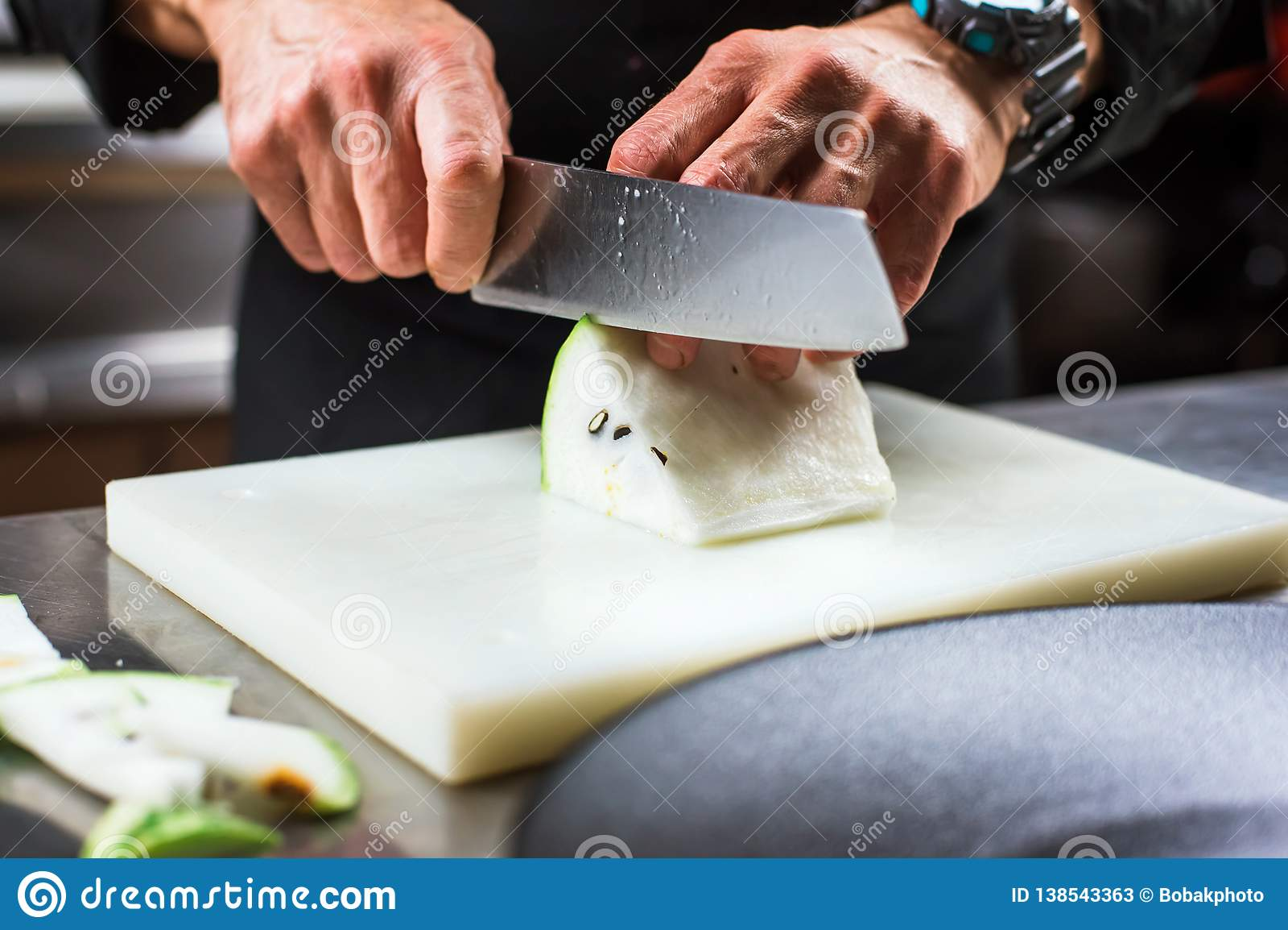 Κινηματογράφηση σε πρώτο πλάνο των αρσενικών χεριών που κόβουν το άσπρο καρπούζι