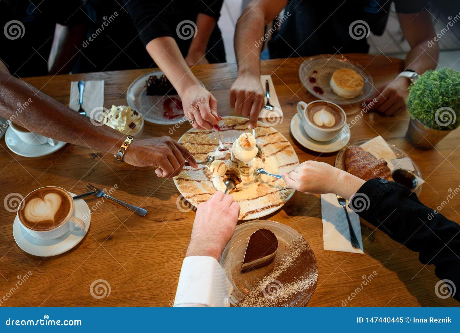 Κινηματογράφηση σε πρώτο πλάνο των πολυφυλετικών χεριών με τα επιδόρπια και των φλυτζανιών καφέ σε έναν καφέ