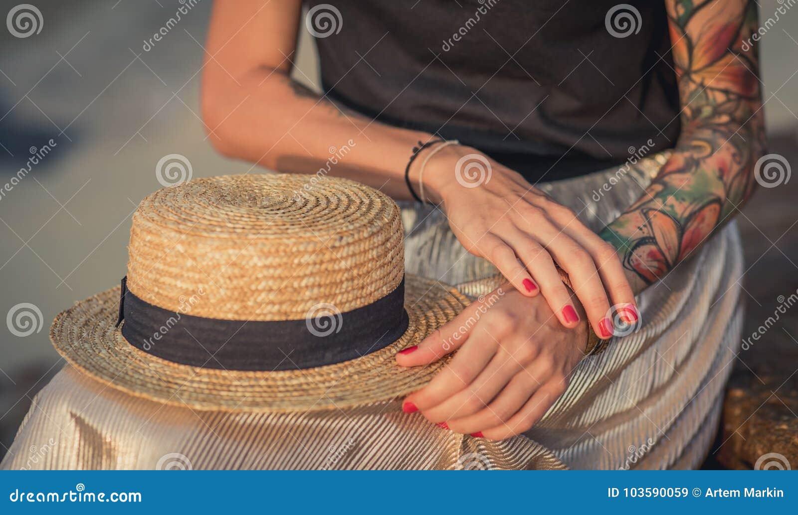 Κινηματογράφηση σε πρώτο πλάνο των υπολοίπων αχύρου καπέλων στα γόνατά του Το θηλυκό χέρι με τις δερματοστιξίες διορθώνει τα βραχ