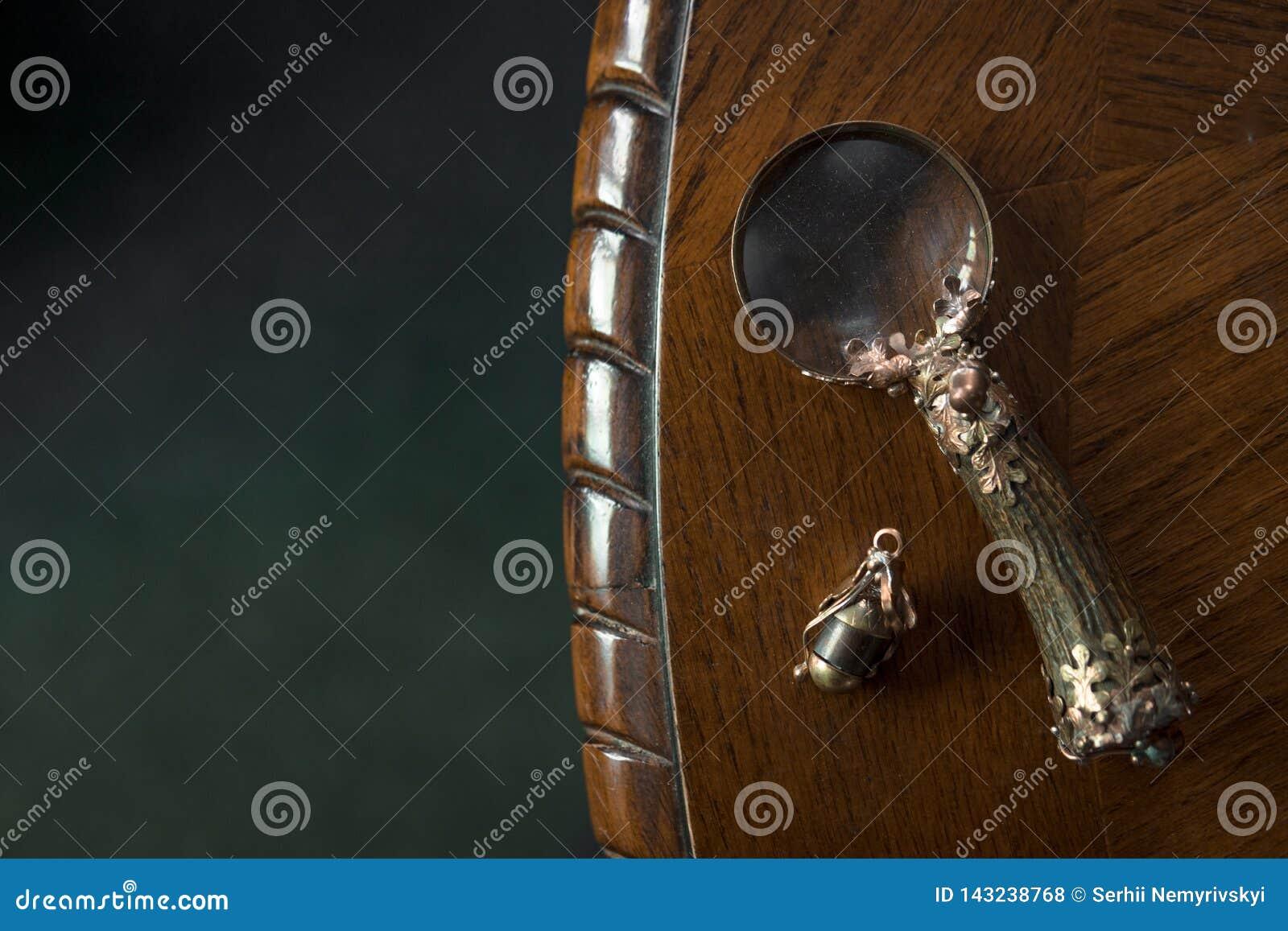 Κινηματογράφηση σε πρώτο πλάνο Loupe, εκλεκτής ποιότητας πιό magnifier χειροποίητος στο σκοτεινό ξύλινο επιτραπέζιο υπόβαθρο, ένν