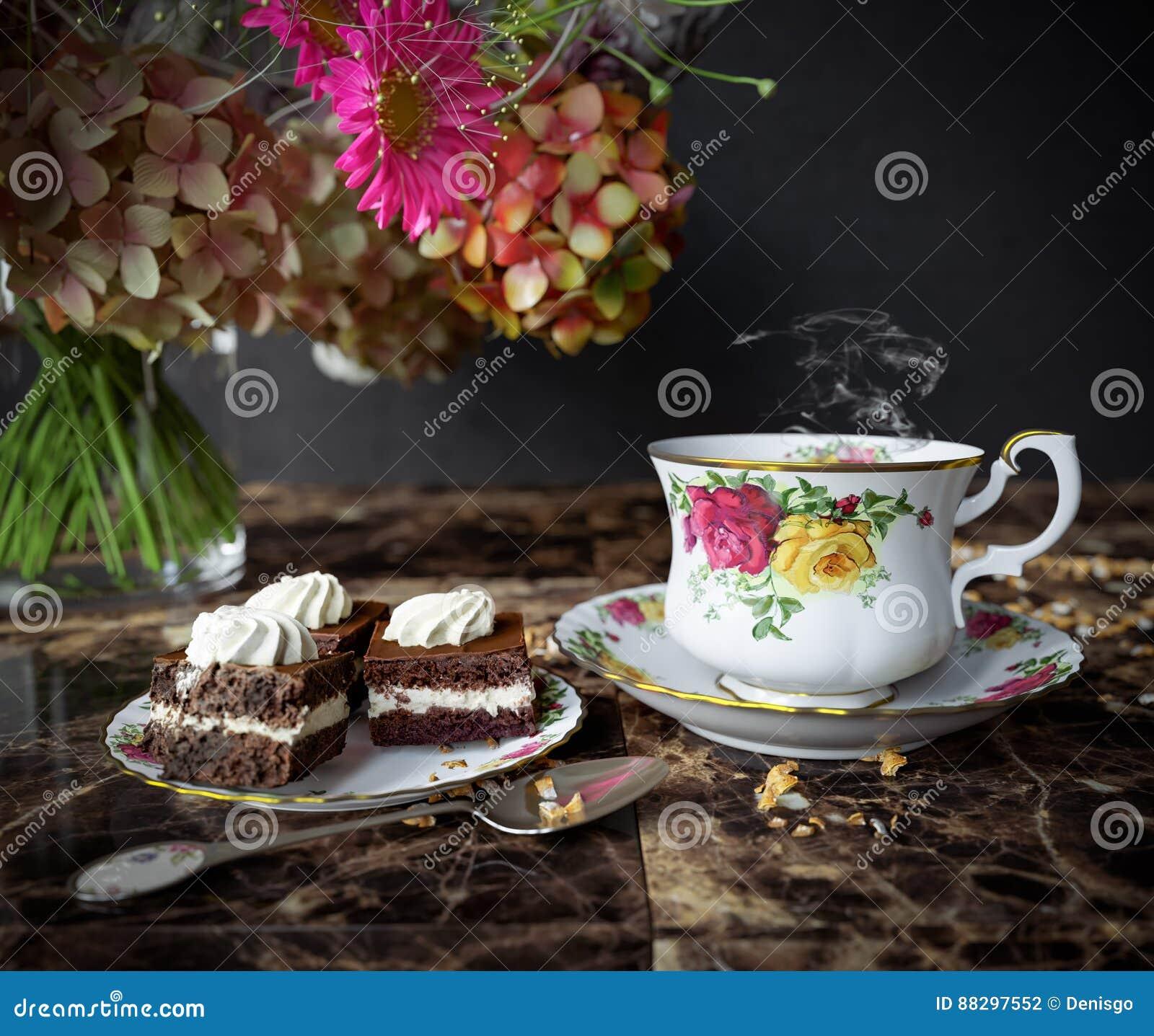 Κινηματογράφηση σε πρώτο πλάνο του φλυτζανιού του τσαγιού με το κέικ και της ανθοδέσμης λουλουδιών στην ξύλινη επιτραπέζια στενή
