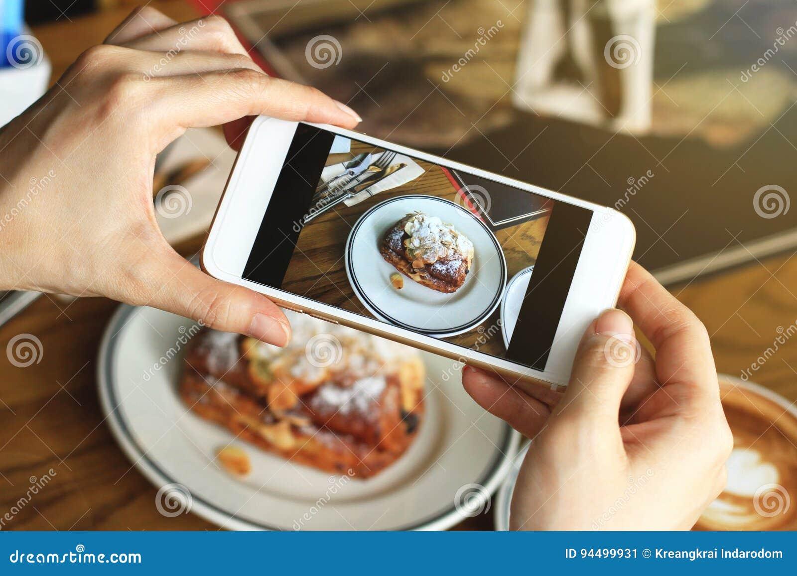Κινηματογράφηση σε πρώτο πλάνο των χεριών γυναικών ` s που παίρνουν τη φωτογραφία του γλυκού επιδορπίου από το smartphone