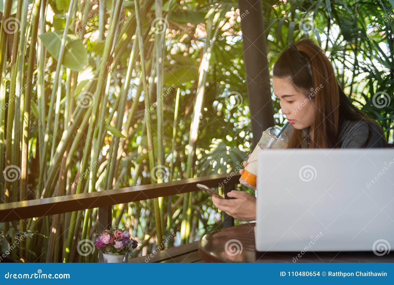 Κινητό τηλέφωνο λαβής γυναικών και κατανάλωση παγωμένο τσάι στη καφετερία, Λα