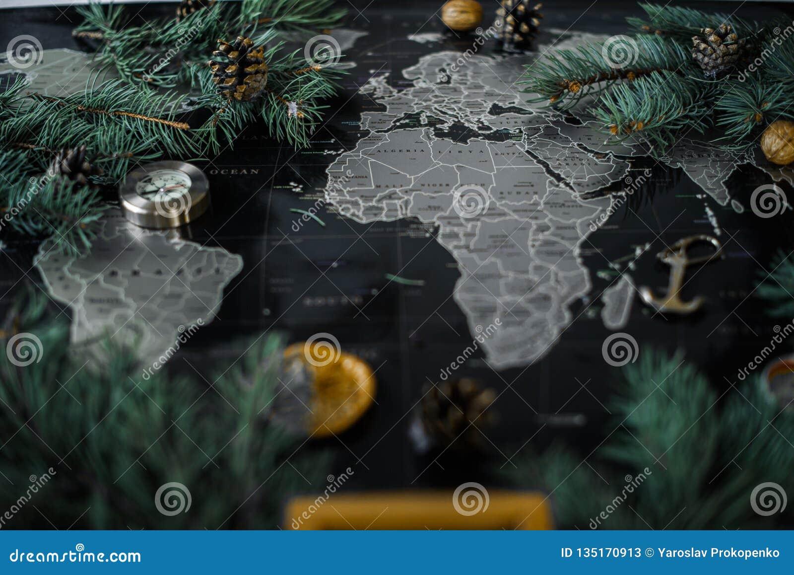 Κλάδοι και πυξίδα χριστουγεννιάτικων δέντρων σε έναν μαύρο χάρτη