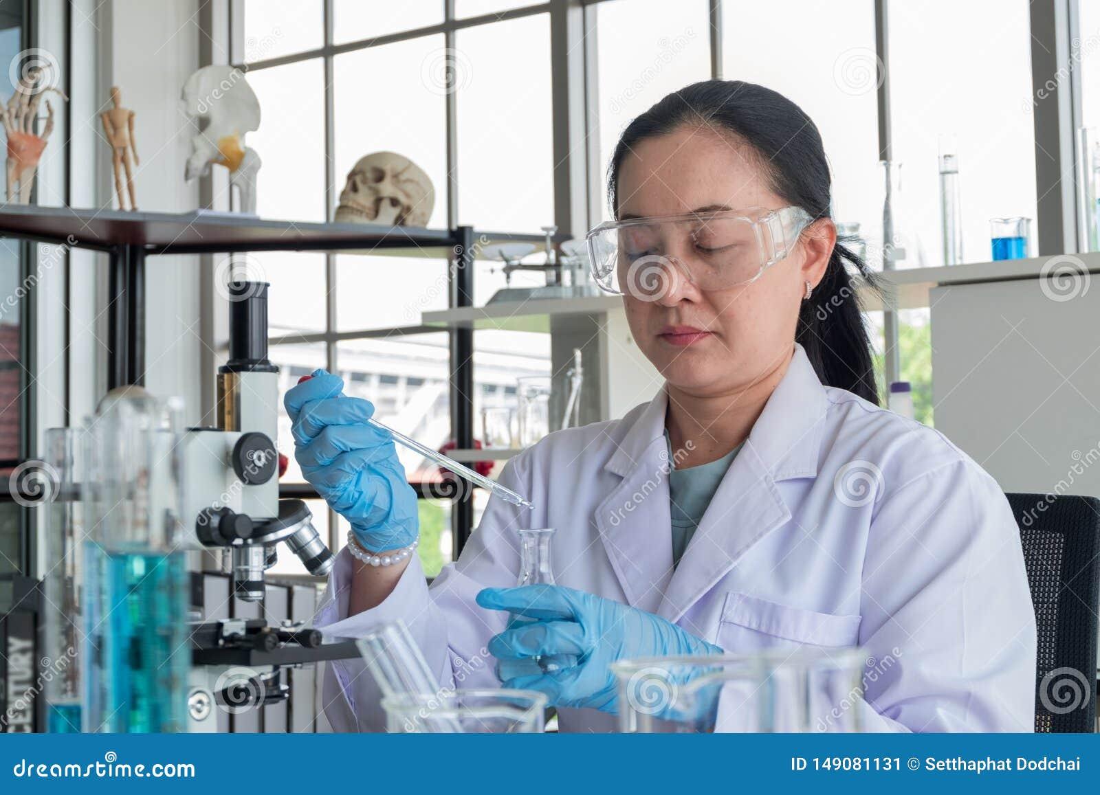 Κλείστε αυξημένος, ασιατικοί θηλυκοί επιστήμονες Μεσαίωνα στο εργαστήριο ο εμπειρογνώμονας, απασχολείται στο σωλήνα δοκιμής κάνει