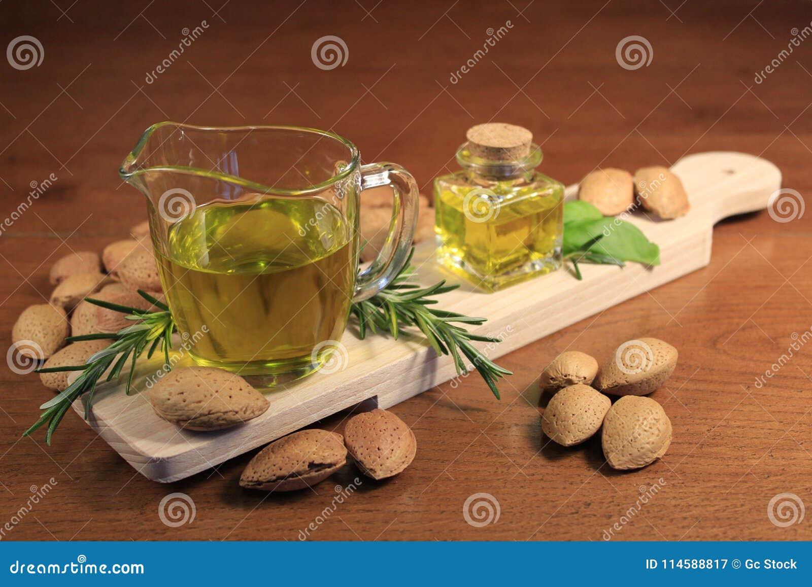 Κλείστε επάνω ενός ποτηριού του πετρελαίου αμυγδάλων με μερικά καρυκεύματα και αμύγδαλα σε έναν ξύλινο τέμνοντα πίνακα