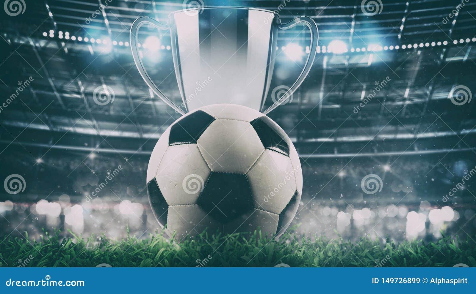 Κλείστε επάνω μιας σφαίρας ποδοσφαίρου με το τρόπαιο στο κέντρο του σταδίου που φωτίζεται από τους προβολείς