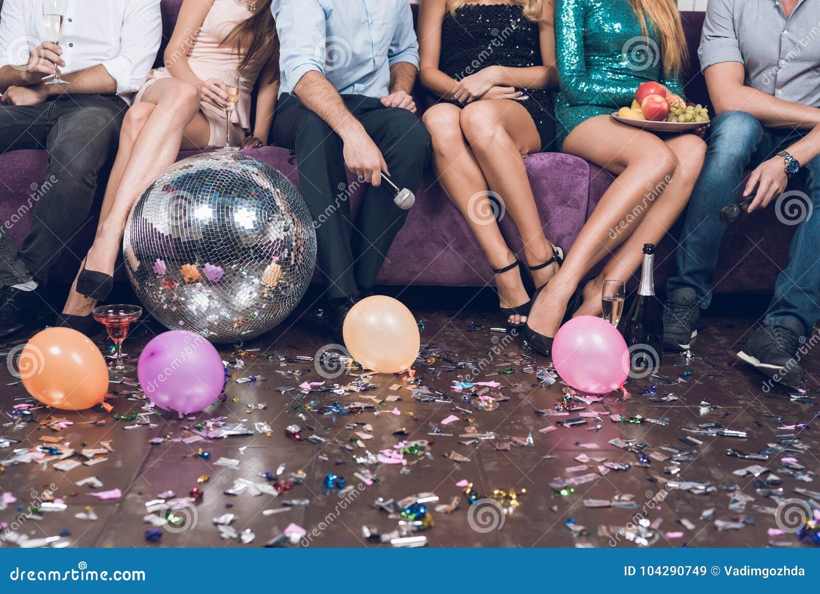 κλείστε επάνω Οι νέοι στηρίζονται ανά τα ζευγάρια σε ένα νυχτερινό κέντρο διασκέδασης Κάθονται σε έναν μεγάλο ιώδη καναπέ