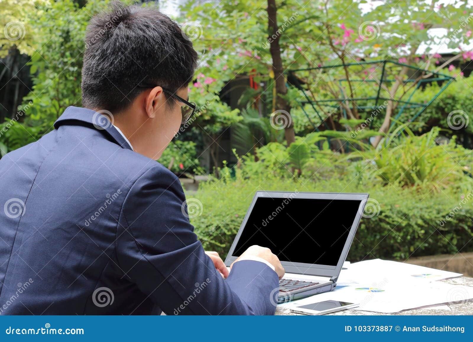Κλείστε επάνω οπισθοσκόπο του όμορφου νέου επιχειρησιακού ατόμου εργάζεται με το υπόβαθρο φύσης lap-top δημόσια