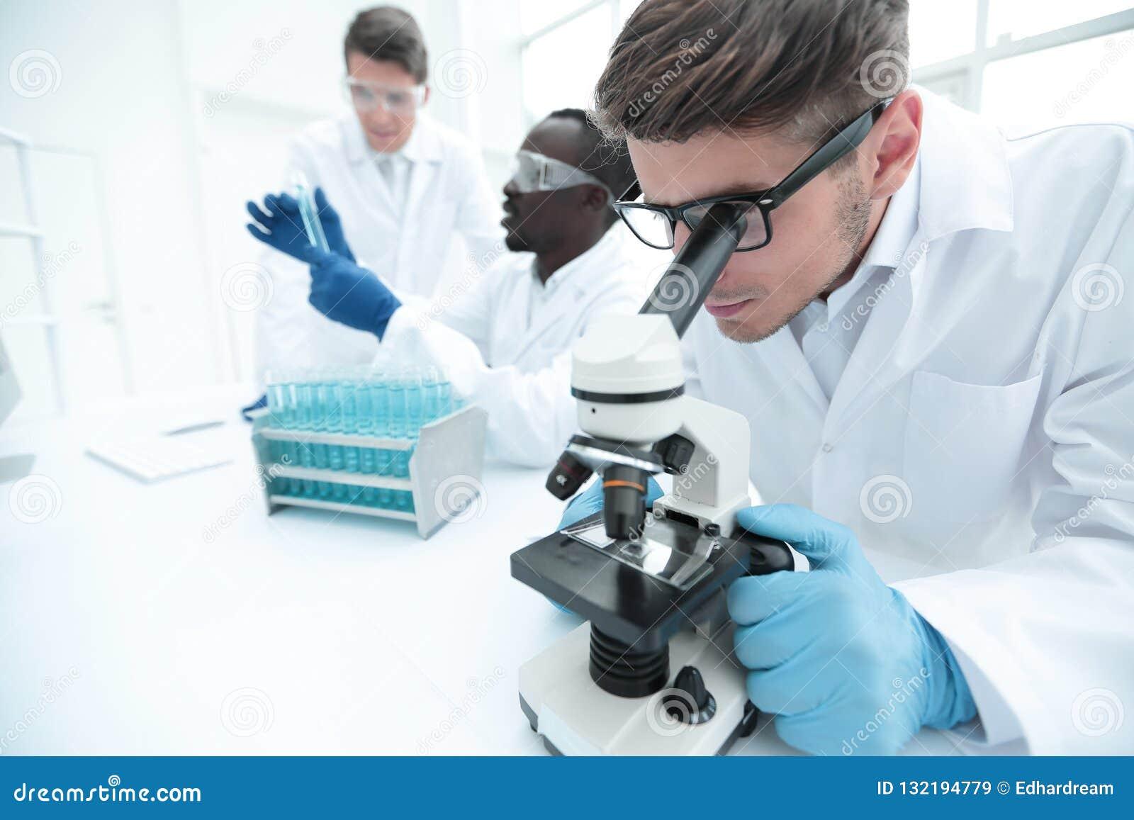 κλείστε επάνω ο επιστήμονας χρησιμοποιεί ένα μικροσκόπιο για την έρευνα