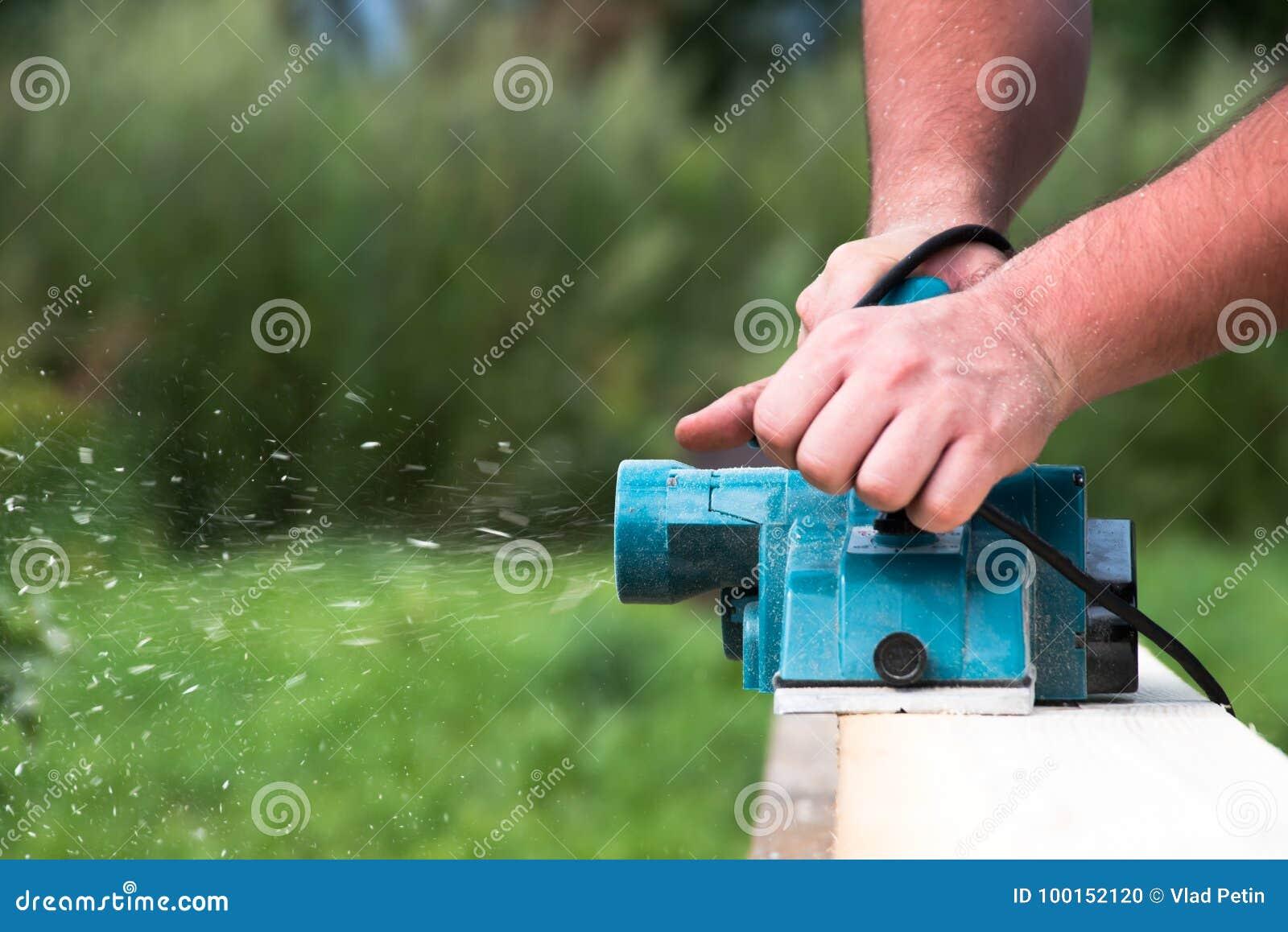 Κλείστε επάνω τα χέρια του ξυλουργού που εργάζεται με την ηλεκτρική μηχανή πλανίσματος στην ξύλινη σανίδα