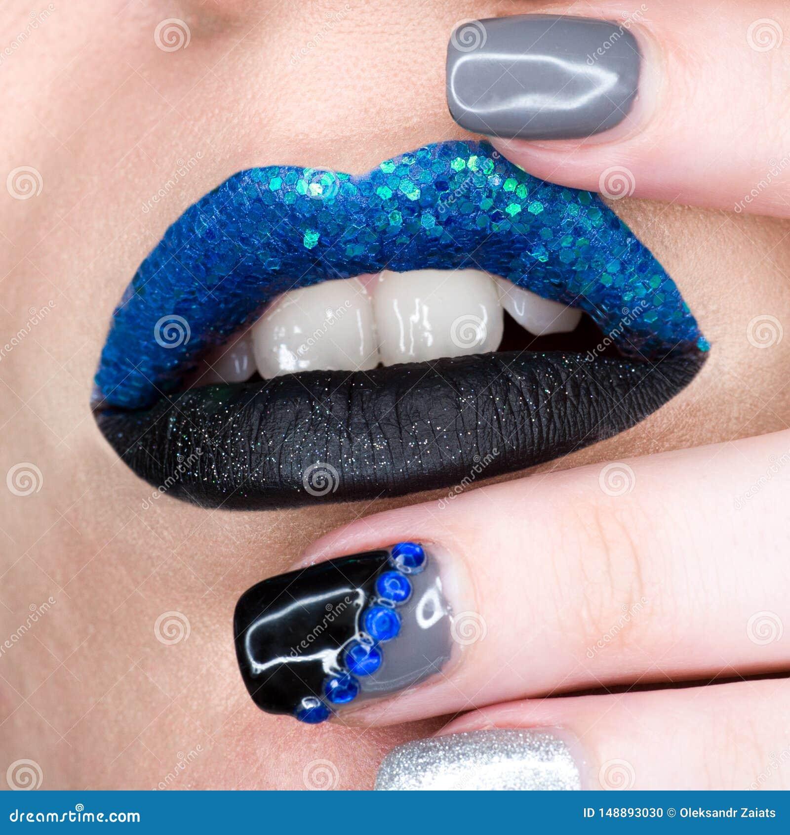 Κλείστε επάνω την άποψη των χειλιών γυναικών με το sparkly μπλε μαύρο ανοικτό στόμα κραγιόν Cosmetology όμορφο μανικιούρ μόδας ma