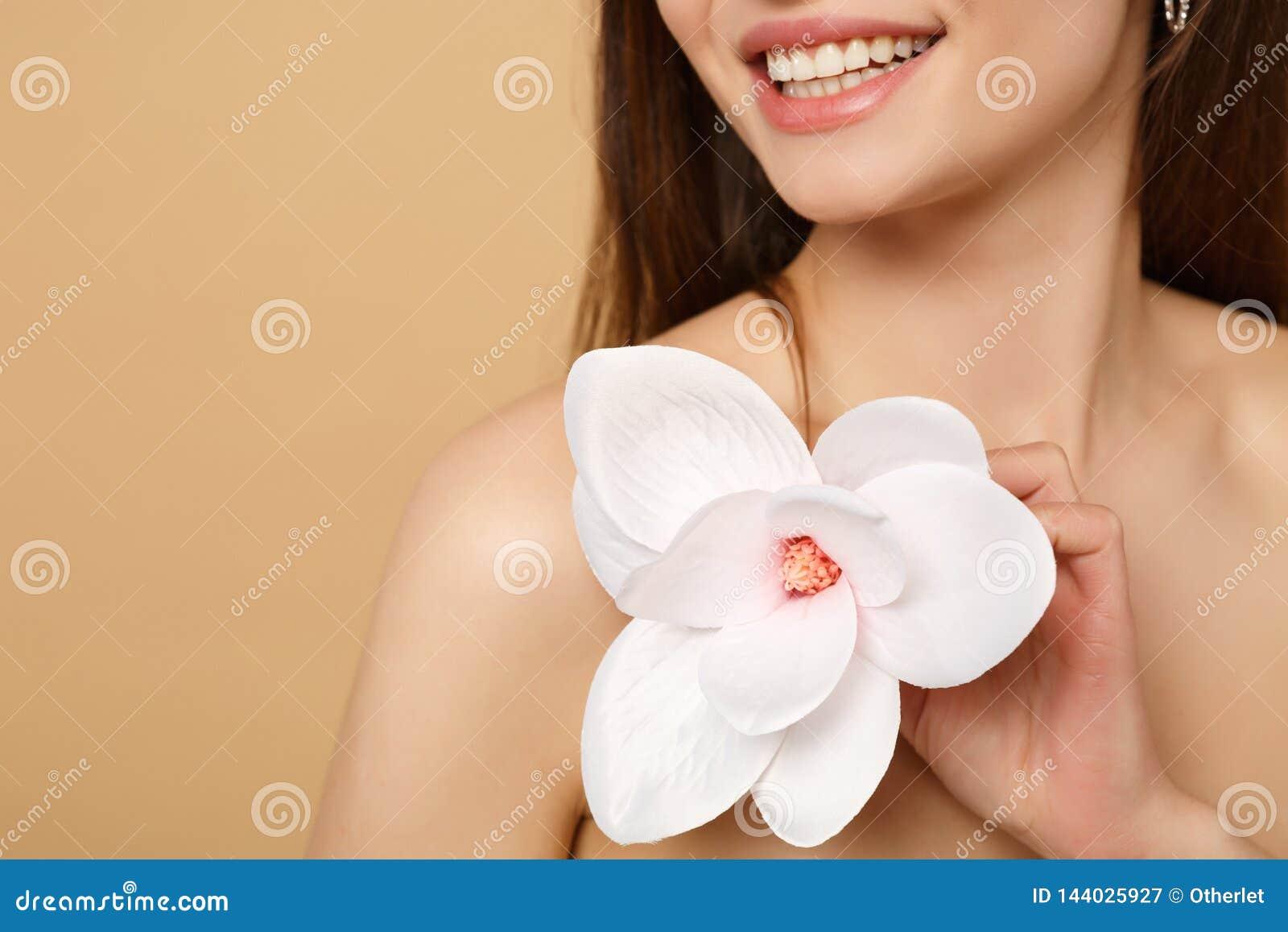 Κλείστε επάνω την ημίγυμνη δεκαετία του  20 γυναικών brunette με το τέλειο δέρμα, nude αποτελέστε απομονωμένος στο μπεζ υπόβαθρο