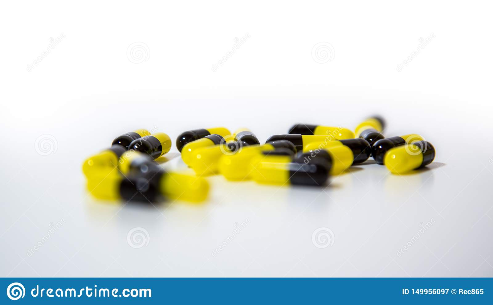 Κλείστε επάνω της μαύρης και κίτρινης ιατρικής χαπιών και ταμπλετών στο άσπρο υπόβαθρο