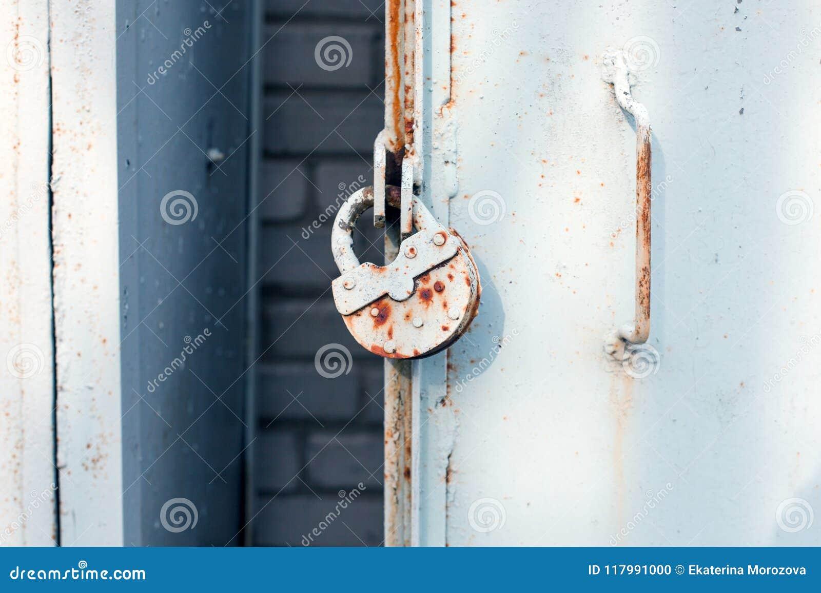 Κλείστε επάνω της πόρτας μετάλλων με την κλειδαριά, βρώμικο ύφος ανασκόπηση βιομηχανική