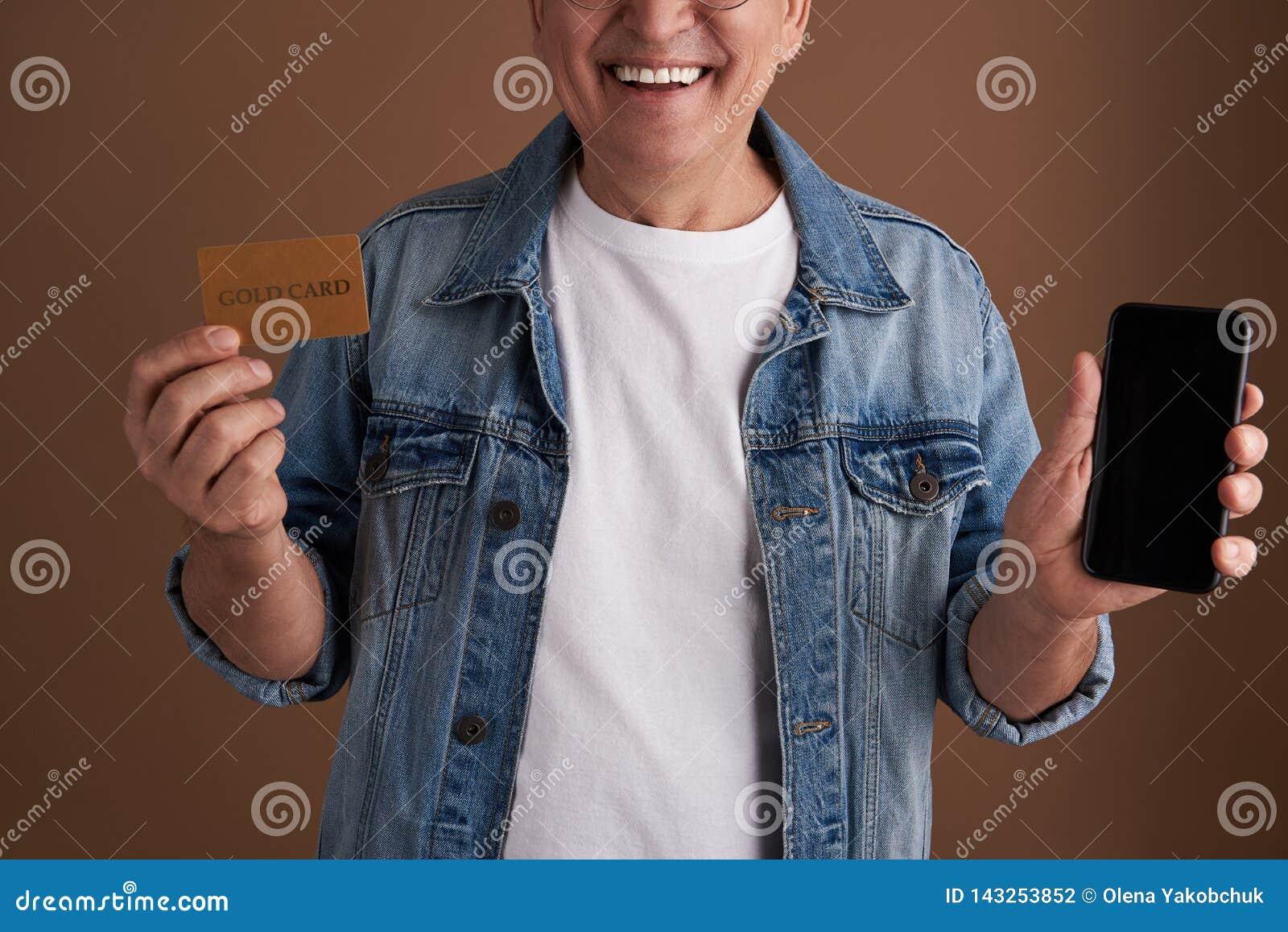 Κλείστε επάνω της χρυσής κάρτας και της σύγχρονης συσκευής στα χέρια του χαμογελώντας ατόμου