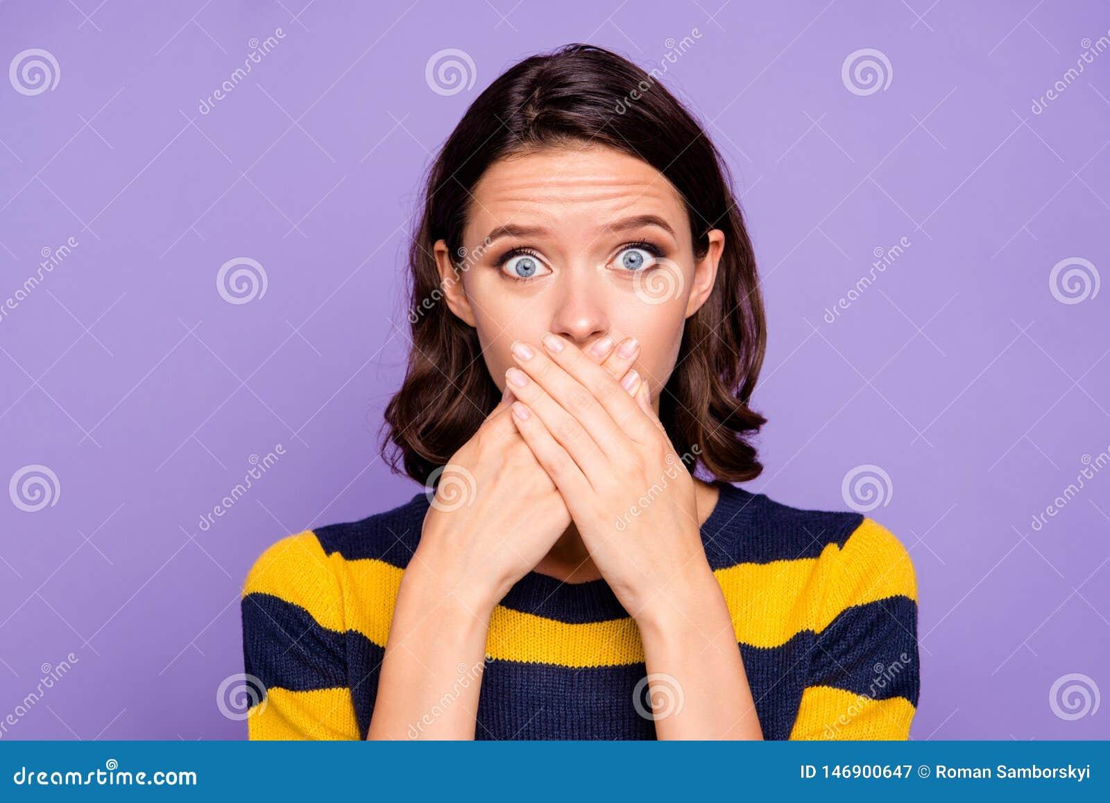Κλείστε επάνω τη φωτογραφία όμορφη που καταπλήσσει αυτή όπλα OH χεριών γυναικείων τα κρύβοντας στομάτων της κανένα μάτι έκφρασης