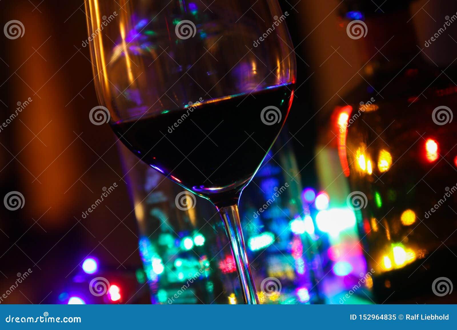Κλείστε επάνω του γυαλιού κόκκινου κρασιού με τα μπουκάλια του οινοπνεύματος και του ζωηρόχρωμου ηλεκτρικού φωτός