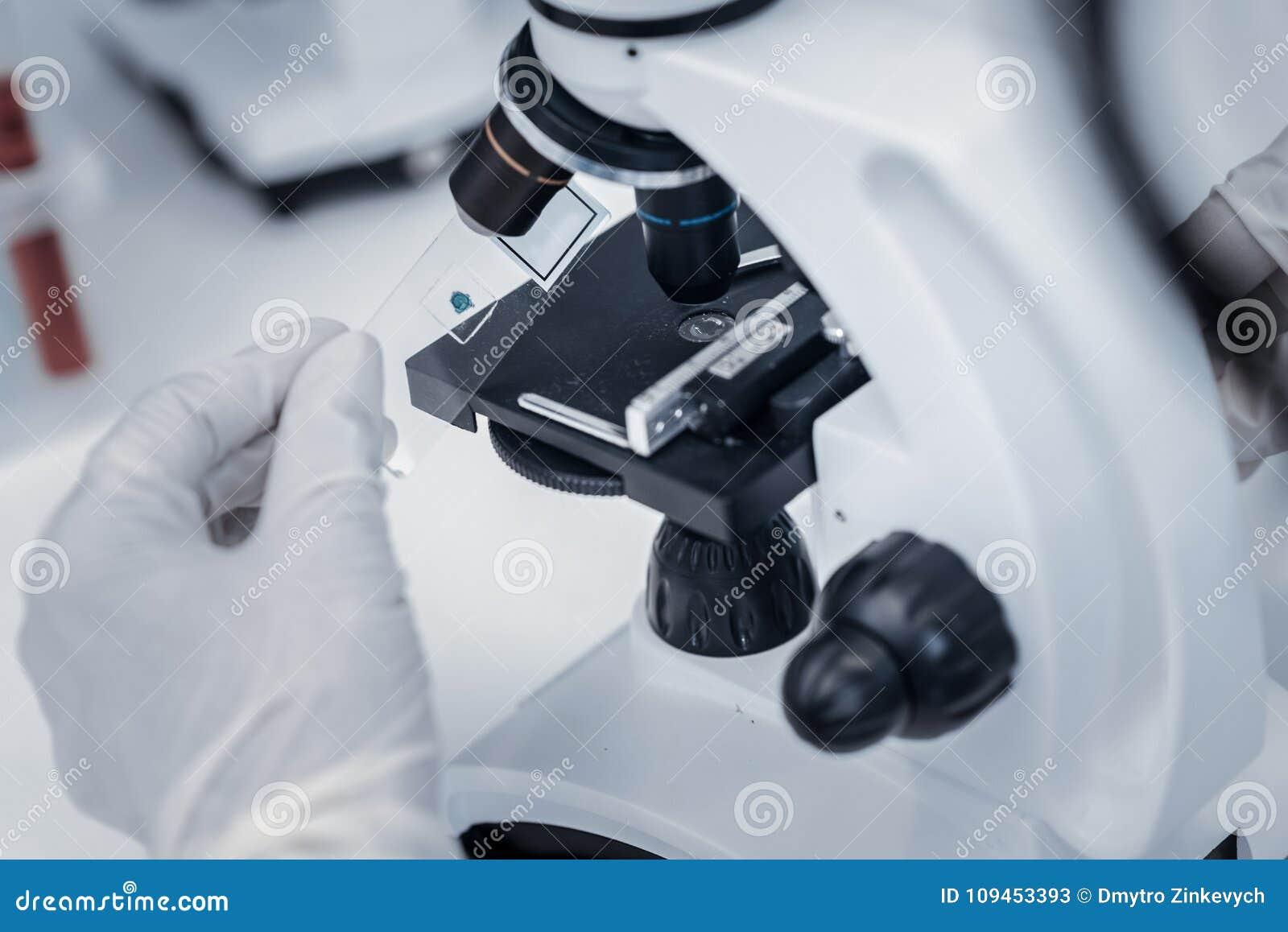 Κλείστε επάνω του ερευνητή που τοποθετεί το δείγμα κάτω από το μικροσκόπιο
