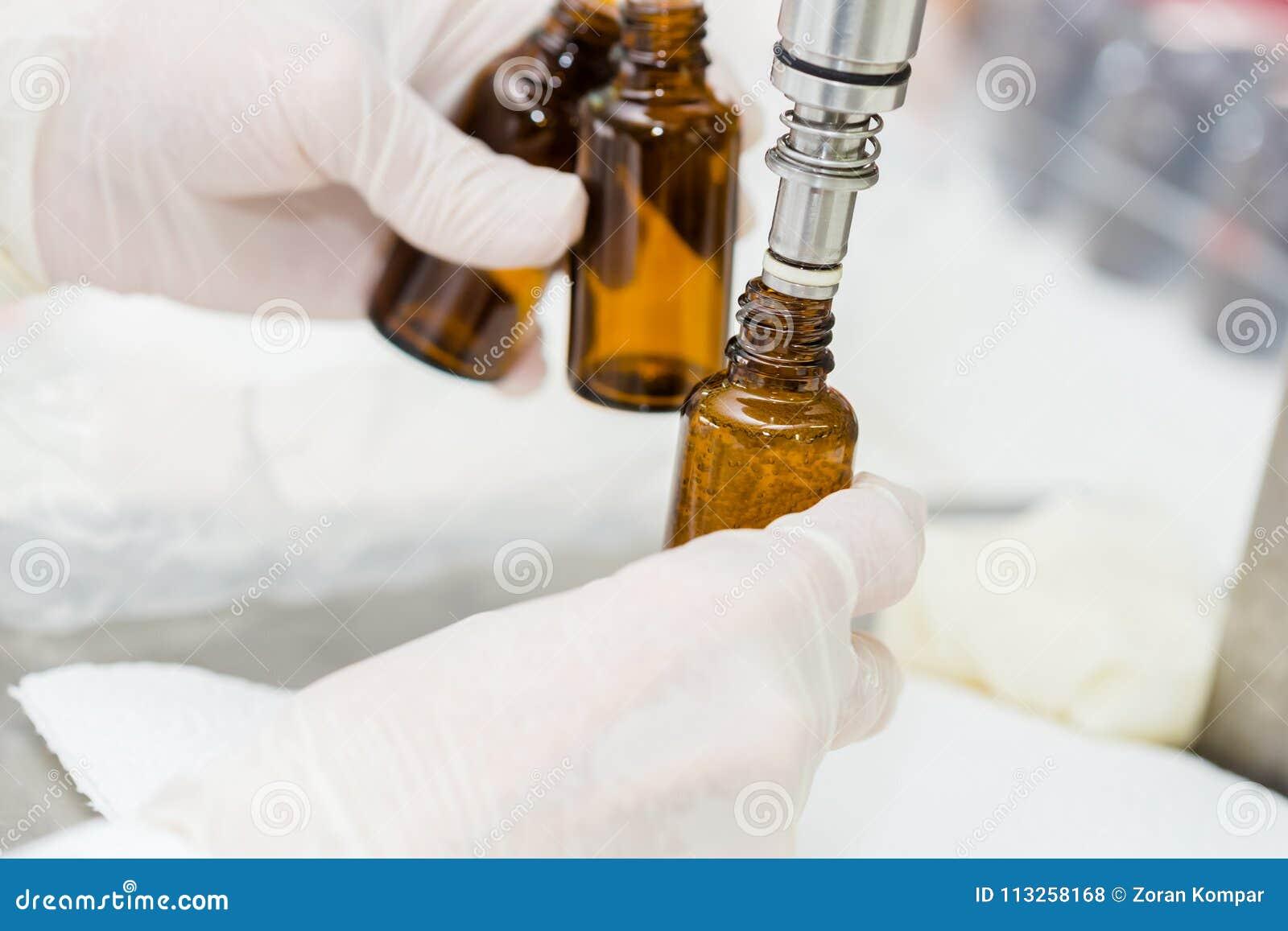 Κλείστε επάνω του θηλυκού χεριού εργαζομένων εργαστηρίων με τα γάντια γεμίζοντας το bottl