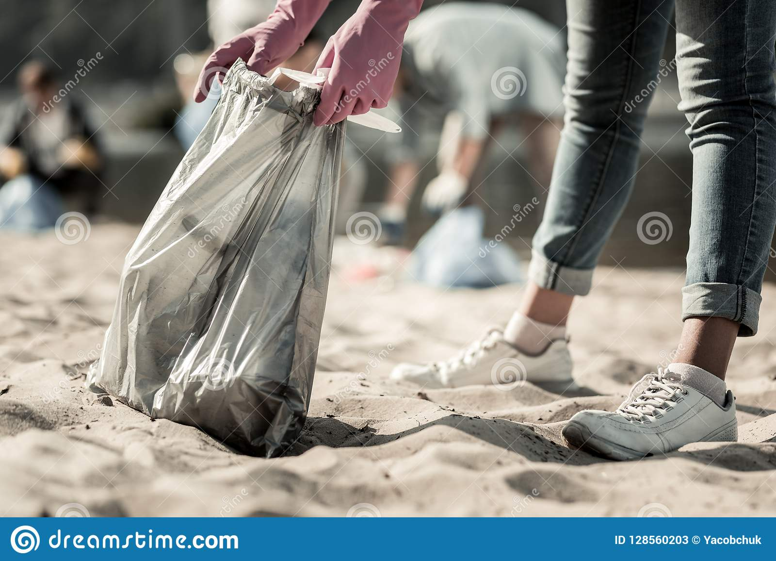 Κλείστε επάνω του νέου σπουδαστή που φορά τα τζιν και τα πάνινα παπούτσια που καθαρίζουν επάνω τα απορρίμματα στην παραλία