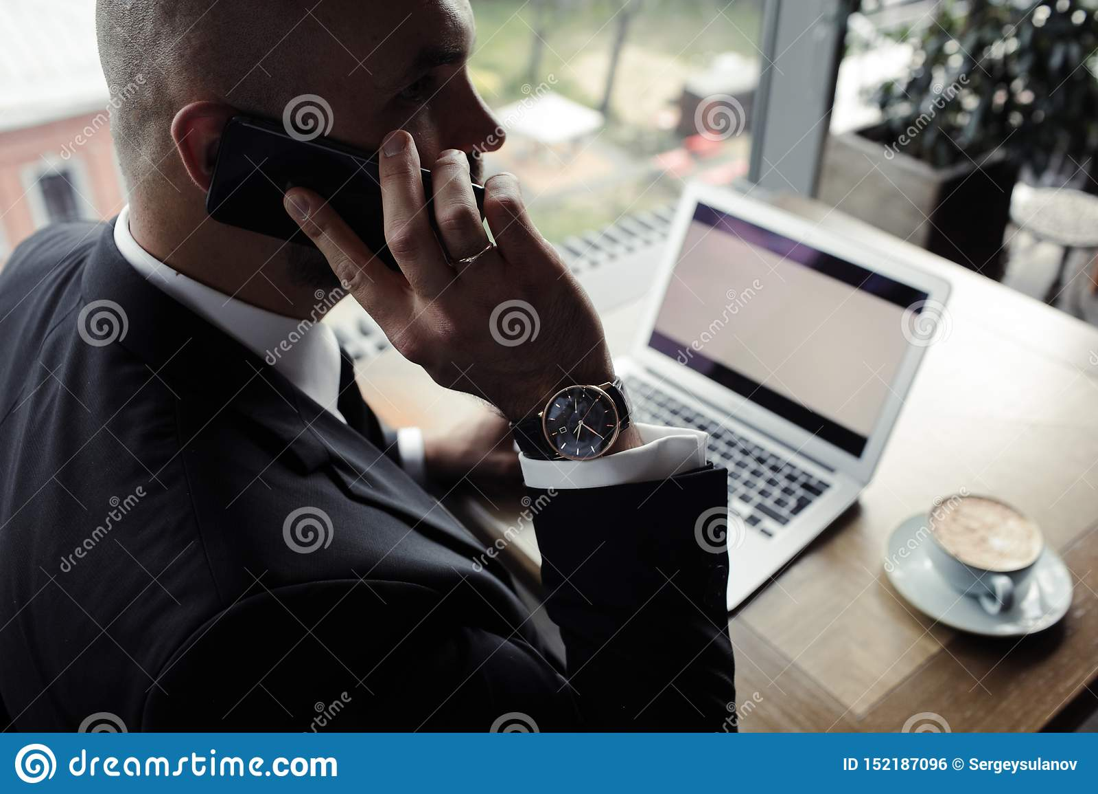 Κλείστε επάνω του όμορφου επιχειρηματία, που εργάζεται στο lap-top στο εστιατόριο