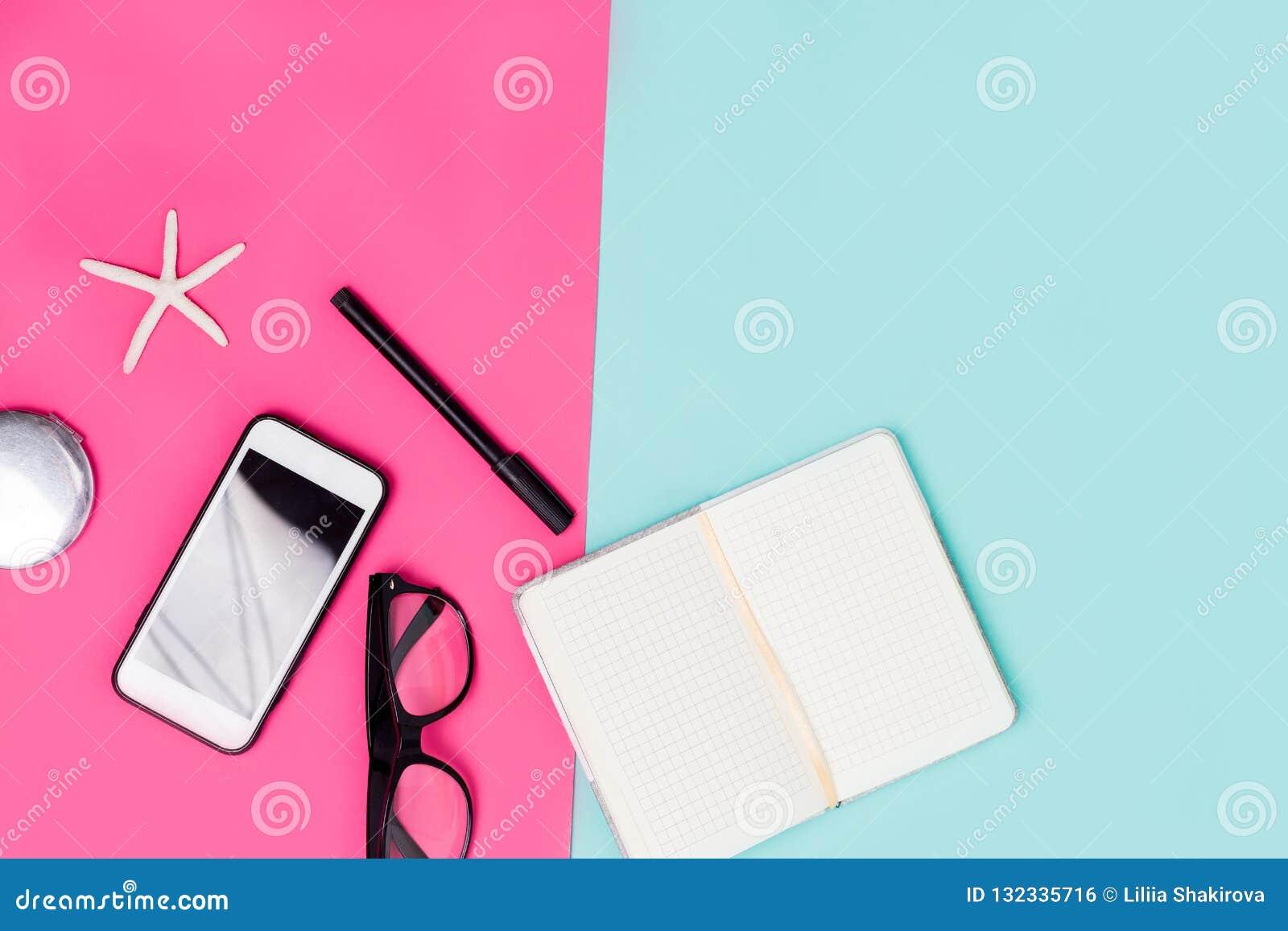 Κλείστε επάνω το γραφείο γραφείων με τα χαρτικά, τα γυαλιά και το smartphone Ροζ άνοιξη και μπλε υπόβαθρο κρητιδογραφιών
