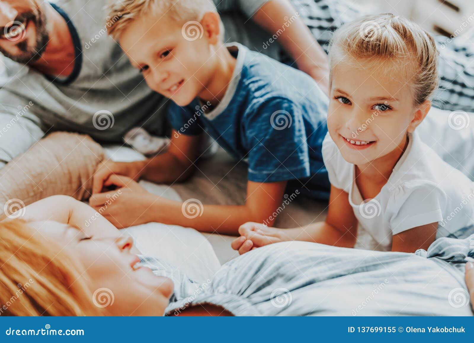 Κλείστε επάνω το ευτυχή κορίτσι και το αγόρι με τους γονείς στο κρεβάτι