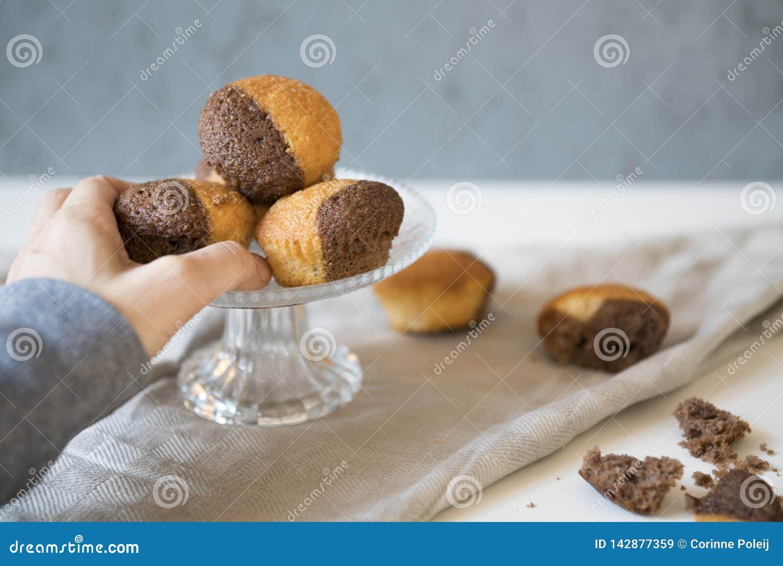 Κλείστε επάνω το πιάτο γυαλιού με τη σοκολάτα βανίλιας cupcakes