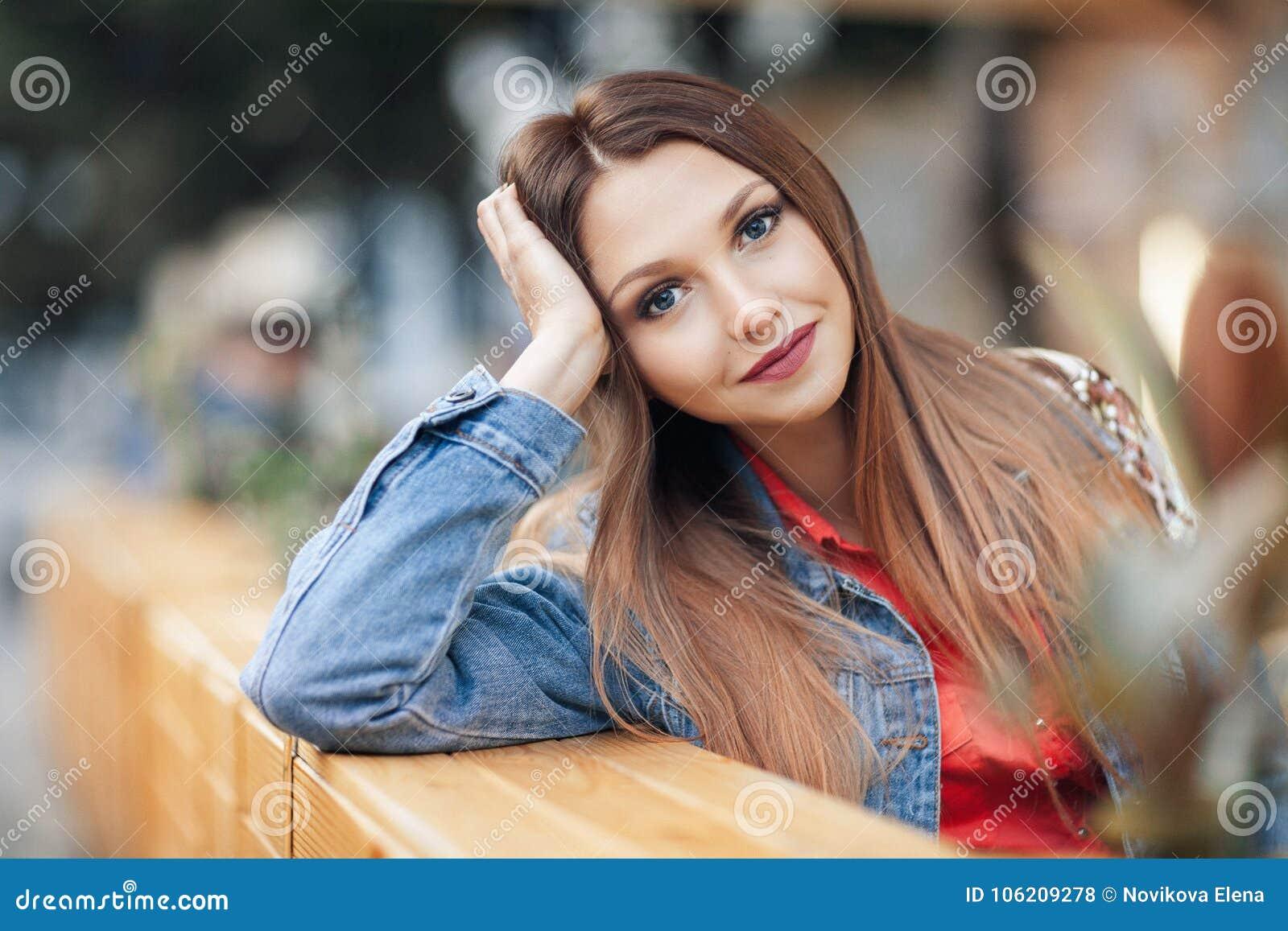 Κλείστε επάνω το πορτρέτο μιας όμορφης ξανθής κοριτσιών συνεδρίασης προσώπου χεριών αδύνατης υπαίθριας στον άνετο καφέ στην πόλη