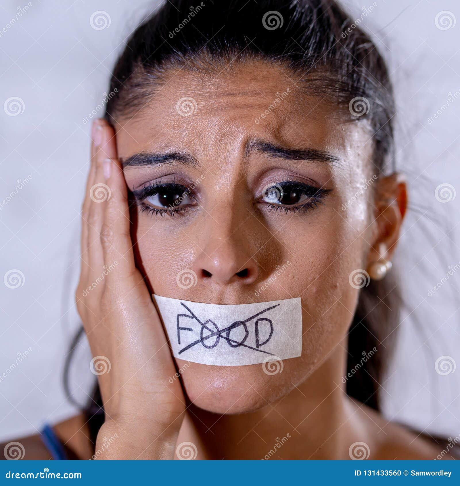 Κλείστε επάνω το πορτρέτο της νέας ελκυστικής λατινικής γυναίκας με το στόμα που δεν σφραγίζεται στην ταινία ραβδιών με το κείμεν