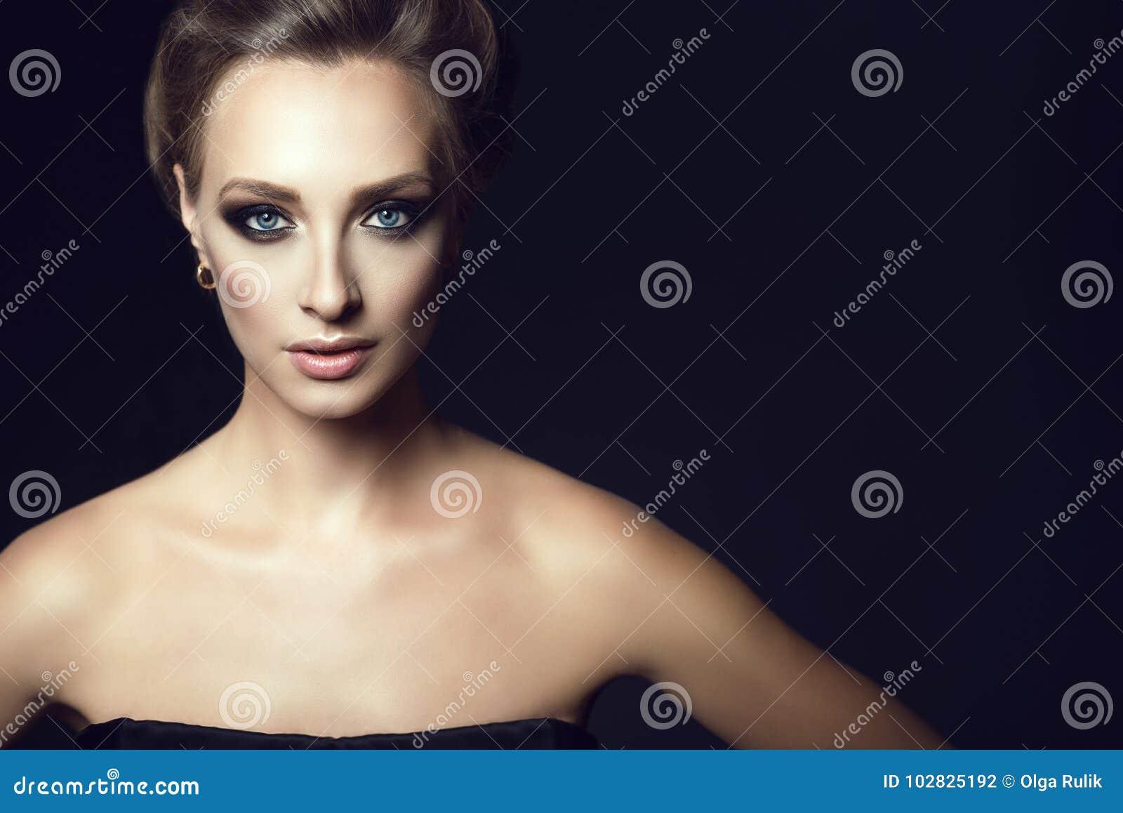 Κλείστε επάνω το πορτρέτο της νέας πανέμορφης γυναίκας με την τρίχα updo και τελειοποιήστε αποτελεί να φανεί ευθύς
