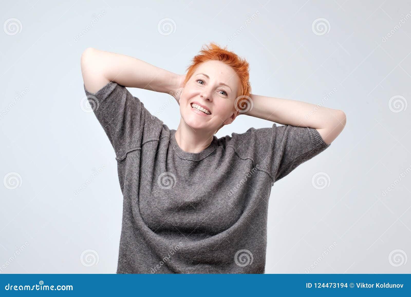 Κλείστε επάνω το πορτρέτο της όμορφης ώριμης γυναίκας με την κόκκινη τρίχα που χαμογελά και που υπερασπίζεται τον τοίχο