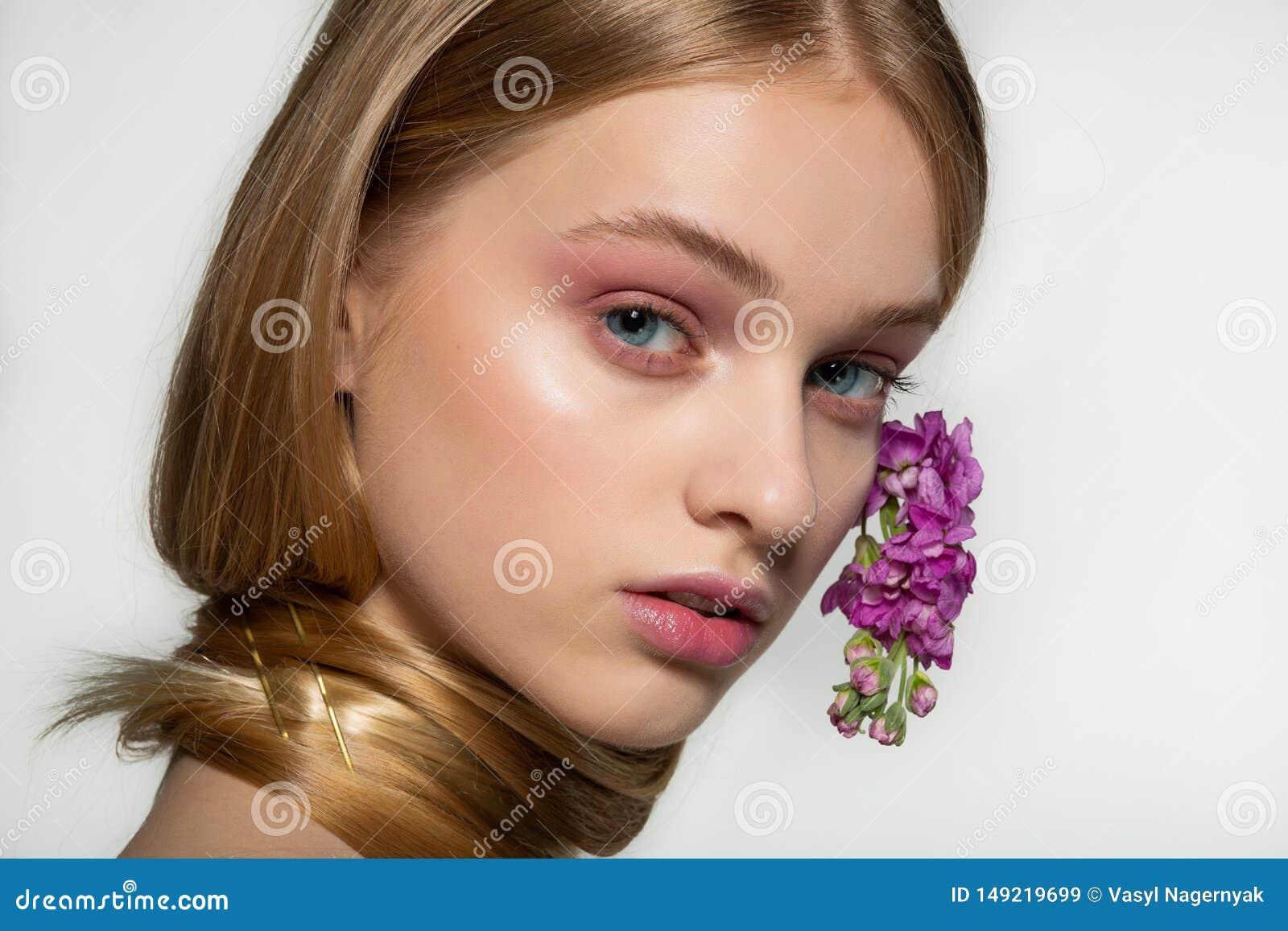 Κλείστε επάνω το πορτρέτο του νέου κοριτσιού με τα μπλε μάτια, φωτεινό makeup, λαιμός που τυλίγεται στην τρίχα, πορφυρά λουλούδια