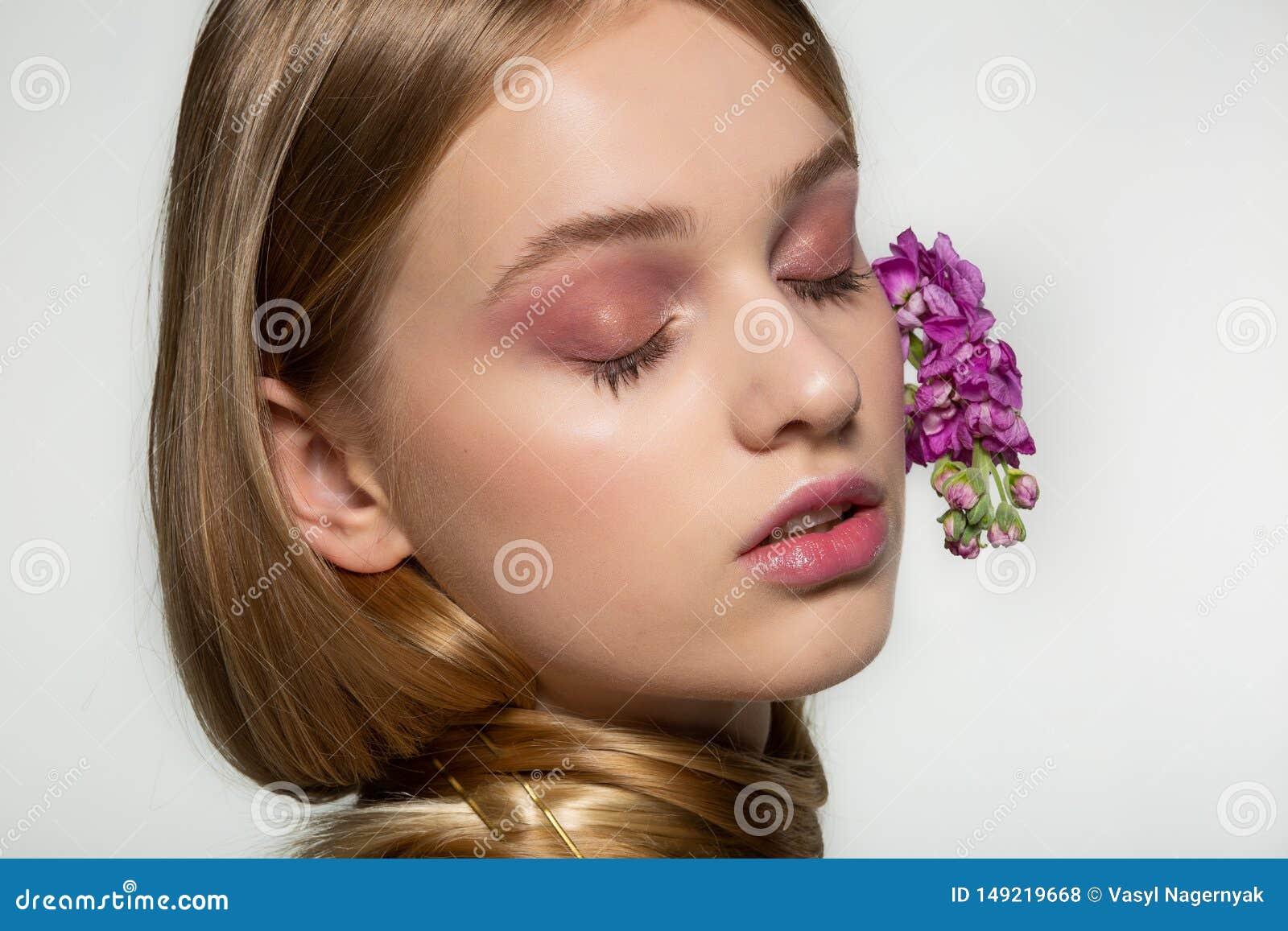Κλείστε επάνω το πορτρέτο του νέου κοριτσιού με τις ιδιαίτερες προσοχές, φωτεινό makeup, λαιμός που τυλίγεται στην τρίχα, πορφυρά