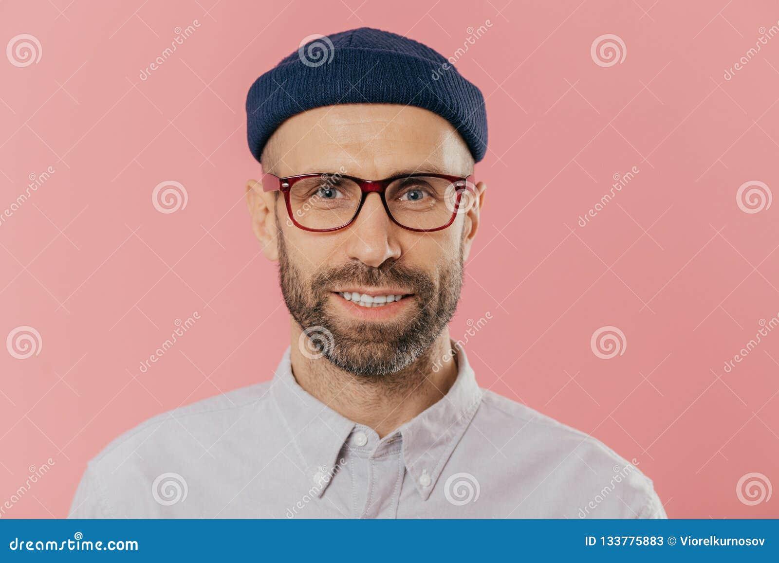 Κλείστε επάνω το πορτρέτο του χαμογελώντας αξύριστου αρσενικού, χαίρεται τις καλές ειδήσεις, φορά το καπέλο και το πουκάμισο, κοι