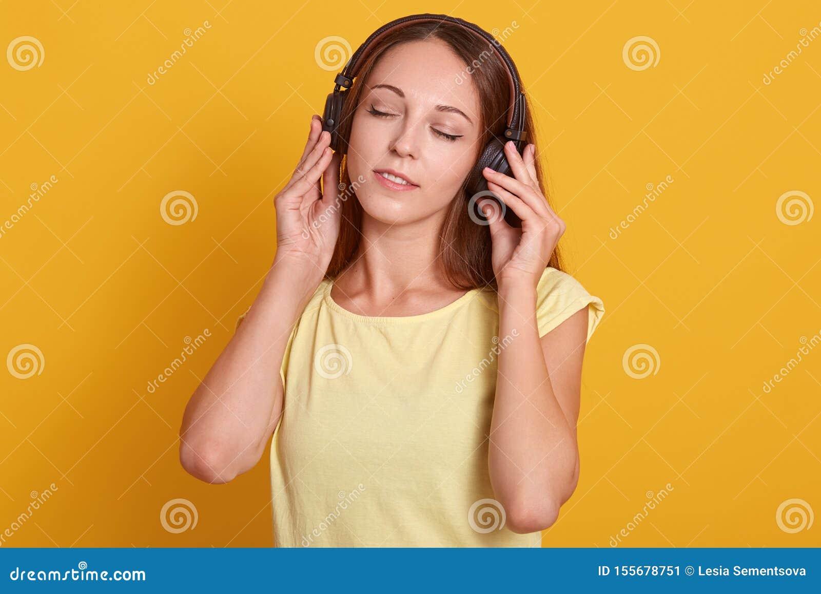 Κλείστε επάνω το πορτρέτο του όμορφου καυκάσιου ακούσματος γυναικών στη μουσική μέσω του ακουστικού, χαλάρωση ενώ έχοντας το ελεύ