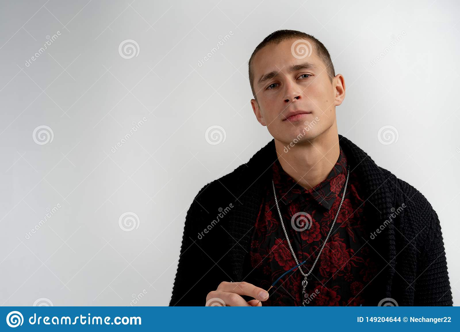 Κλείστε επάνω το πορτρέτο του όμορφου σοβαρού ατόμου της σύγχρονης εμφάνισης με το σύντομο κούρεμα στο μαύρο πουλόβερ που απομονώ