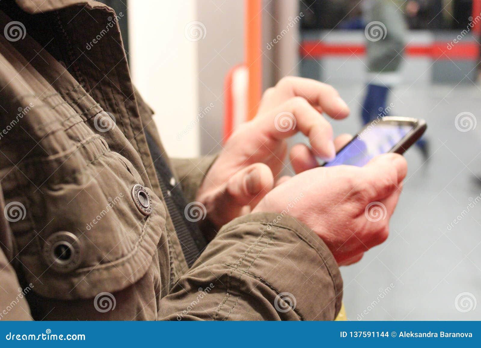 κλείστε επάνω των αρσενικών χεριών χρησιμοποιώντας ένα smartphone