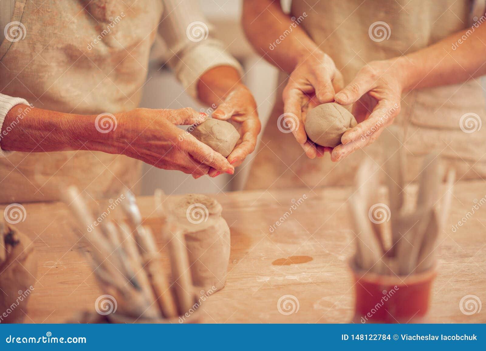 Κλείστε επάνω των σφαιρών αργίλου στα ανθρώπινα χέρια