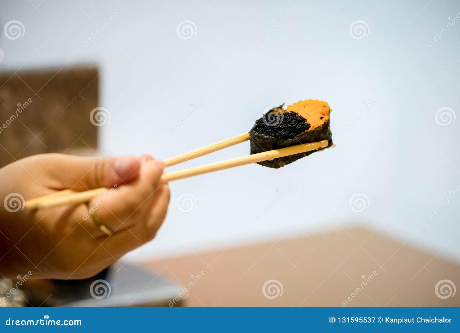 Κλείστε επάνω chopsticks τη λαβή στα ιαπωνικά τρόφιμα γαρίδων αυγών σουσιών για υγιή σούσια unagi, επιλογές σουσιών ασφαλίστρου