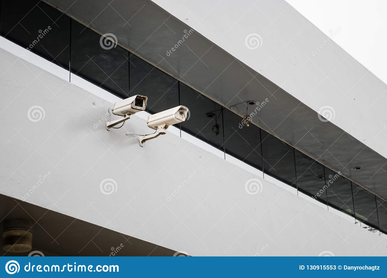 Κλείστε μέχρι δύο κάμερα ασφαλείας στη δομή ενός κτηρίου με έναν μεγάλο καθρέφτη επάνω από τους
