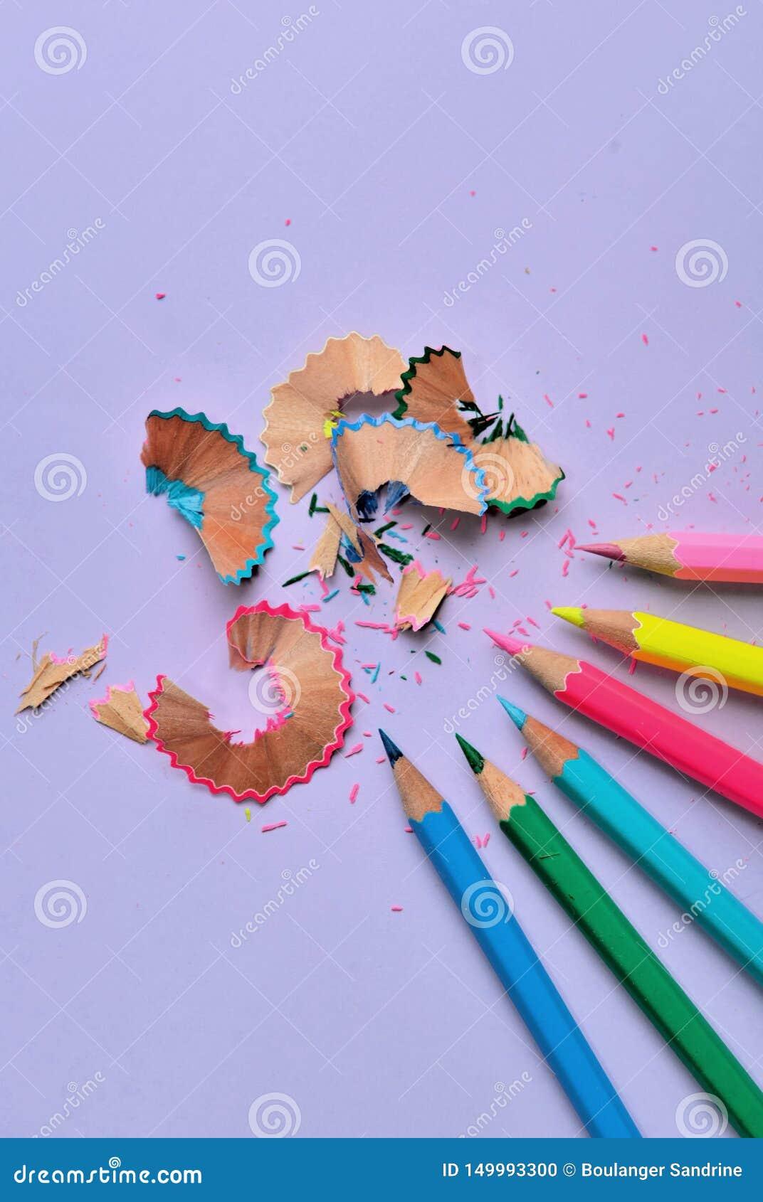 Κλείστε στα ξύλινα ζωηρόχρωμα μολύβια που ακονίζονται σε μωβ χαρτί