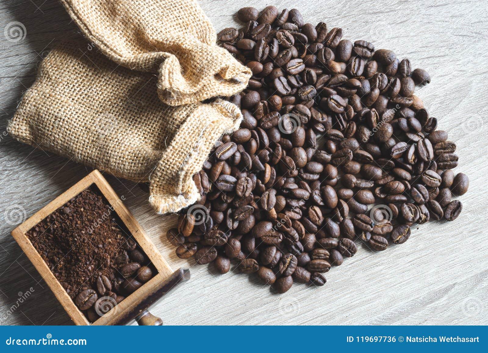 Κλείστε τα επάνω ψημένα φασόλια καφέ με το μικρό σάκο και το συντριμμένο φασόλι