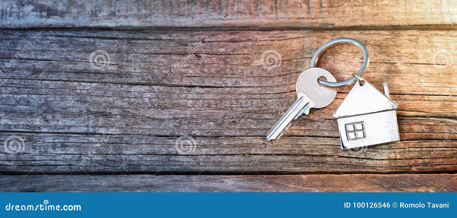 Κλειδί και Keychain σπιτιών στο ξύλο