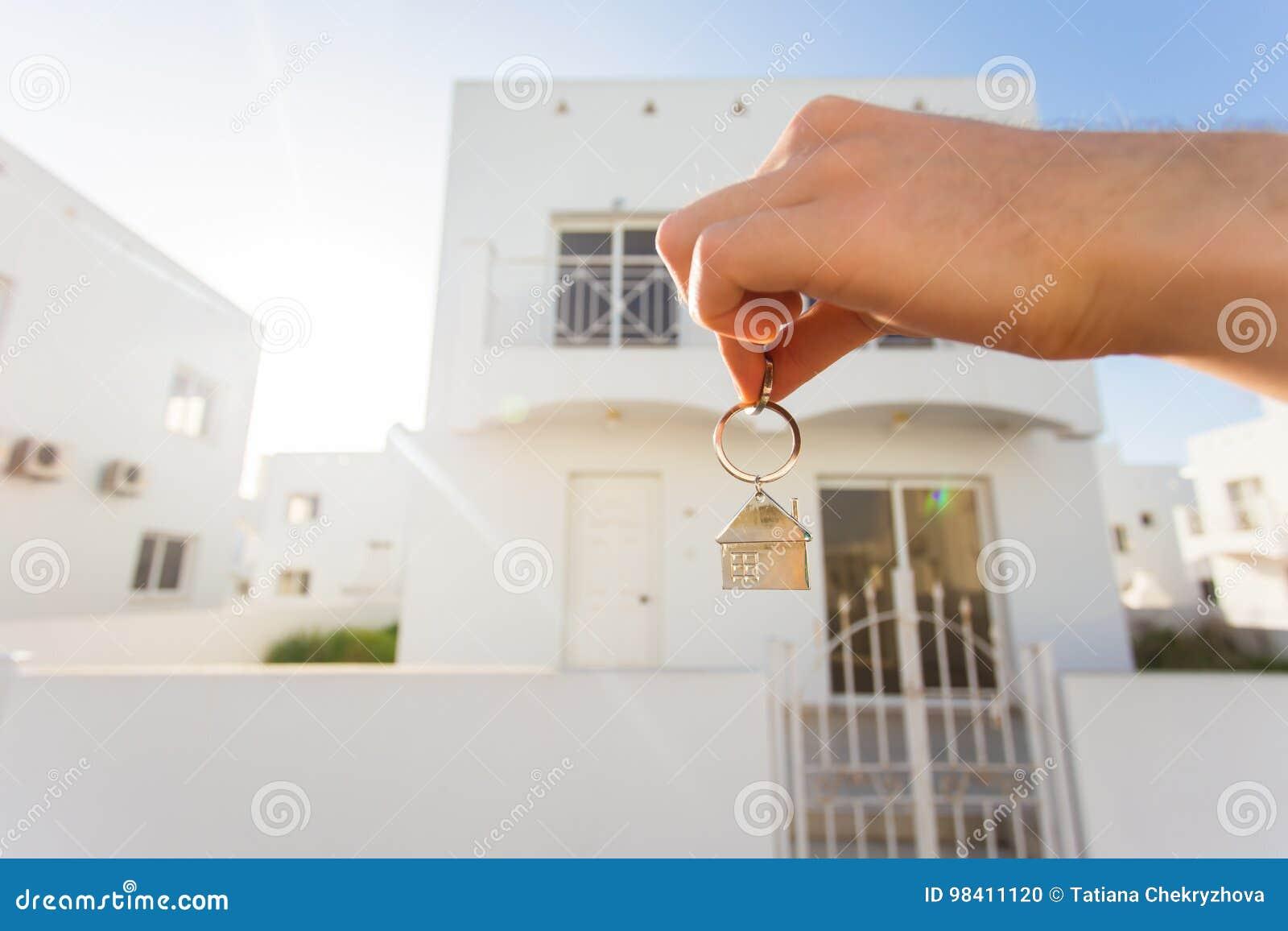 Κλειδιά σπιτιών εκμετάλλευσης διαμορφωμένη στη σπίτι keychain κινηματογράφηση σε πρώτο πλάνο μπροστά από ένα νέο σπίτι κτήμα έννο