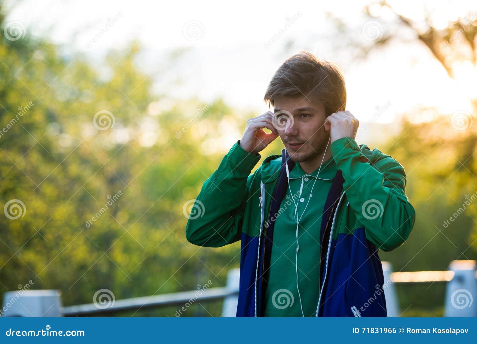 Κοινός νεαρός άνδρας που περπατά στην πόλη που ακούει στη μουσική με τα ακουστικά -αυτιών στο ηλιοβασίλεμα Θέμα μουσικής στο σχέδ