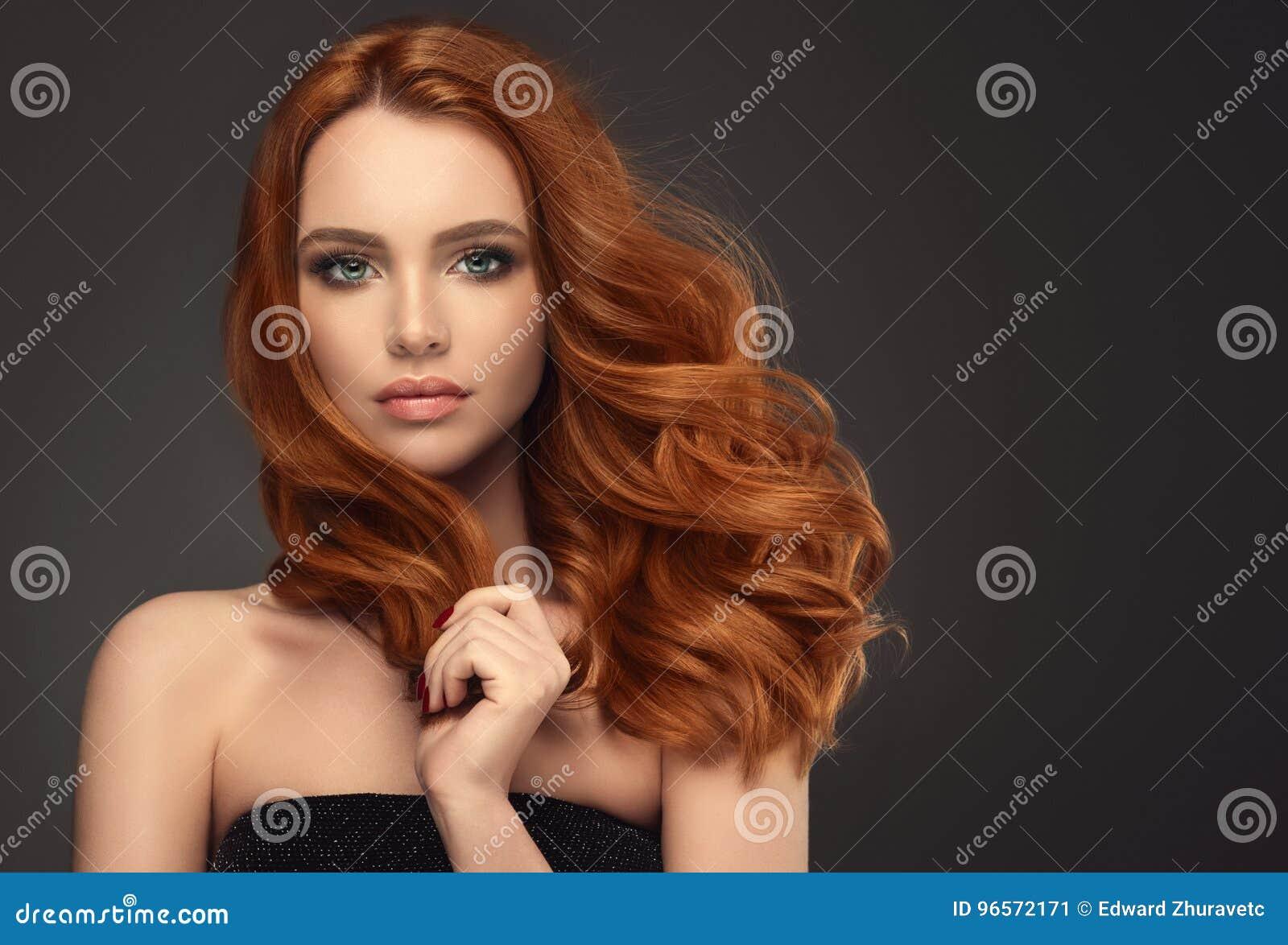 Κοκκινομάλλης γυναίκα με το ογκώδες, λαμπρό και σγουρό hairstyle Σγοuρή τρίχα
