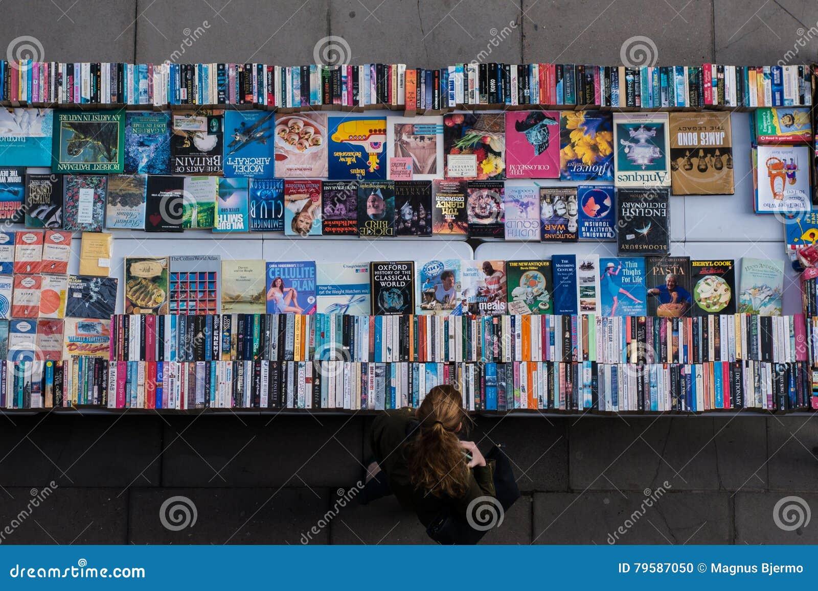Κοκκινομάλλης γυναίκα που κοιτάζει βιαστικά τα μεταχειρισμένα βιβλία στο bookmarket