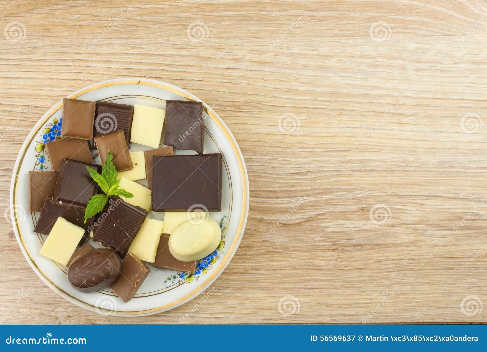 Download Κομμάτια της σοκολάτας σε έναν ξύλινο πίνακα Στοκ Εικόνα - εικόνα από καραμέλα, αδελφών: 56569637